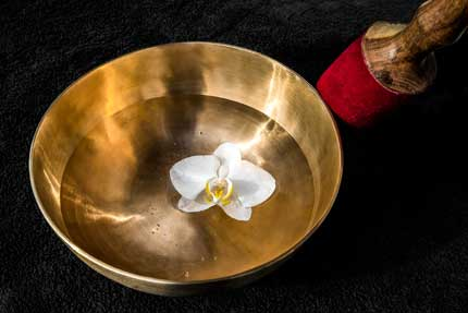 Klangschale mit Orchideenblüte